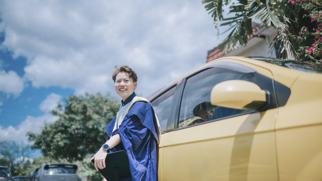 asian chinese young female with graduation gown leaning on her car looking at camera smiling