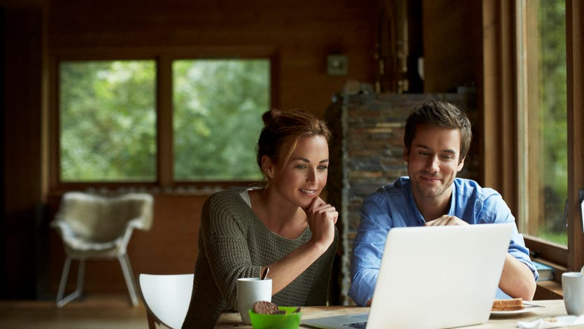 A young couple look at their laptop computer in a cottage