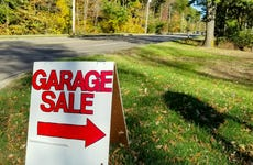 Garage sale in grass on street curb with autumn trees background