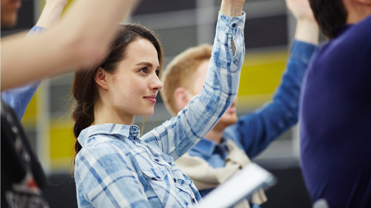 College student raises a hand in a class