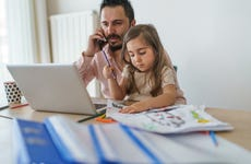 A father and daughter sit at a table while he talks on his phone and she draws.