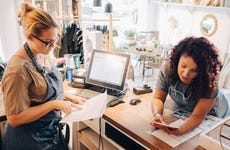 Small business owners review paperwork at shop counter