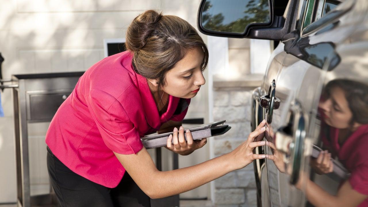 Automobile insurance adjuster inspecting damage to vehicle