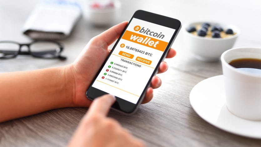 A user holds a phone with the Bitcoin Wallet app