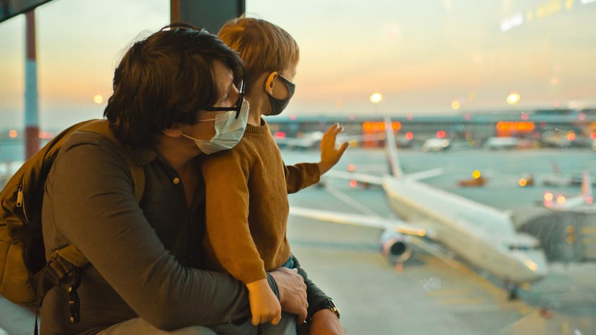 Father and son at airport wearing masks