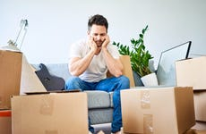Frustrated man sitting on couch surrounded by cardboard boxes
