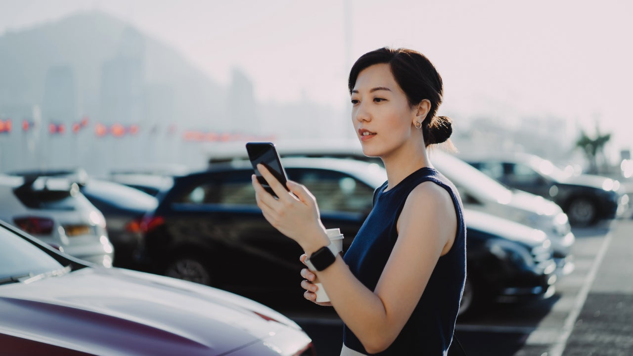 Confident and professional young Asian businesswoman walking to her car in an outdoor carpark in the city, using smartphone and holding a cup of coffee. Business on the go concept