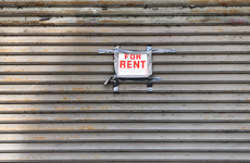 For Rent sign taped on gated storefront, Queens, New York