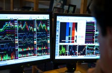 A picture of two trading screens with stock charts on them