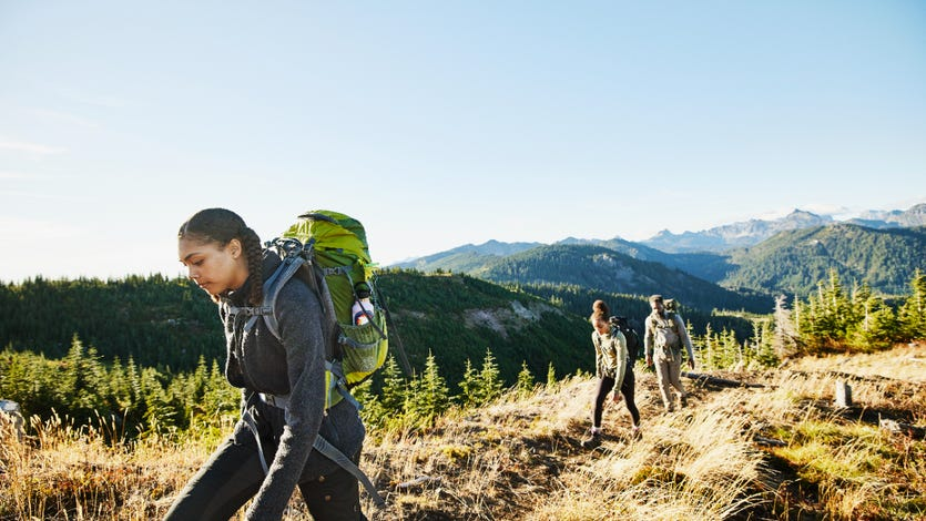 Young woman leading sister and father on backpacking trip