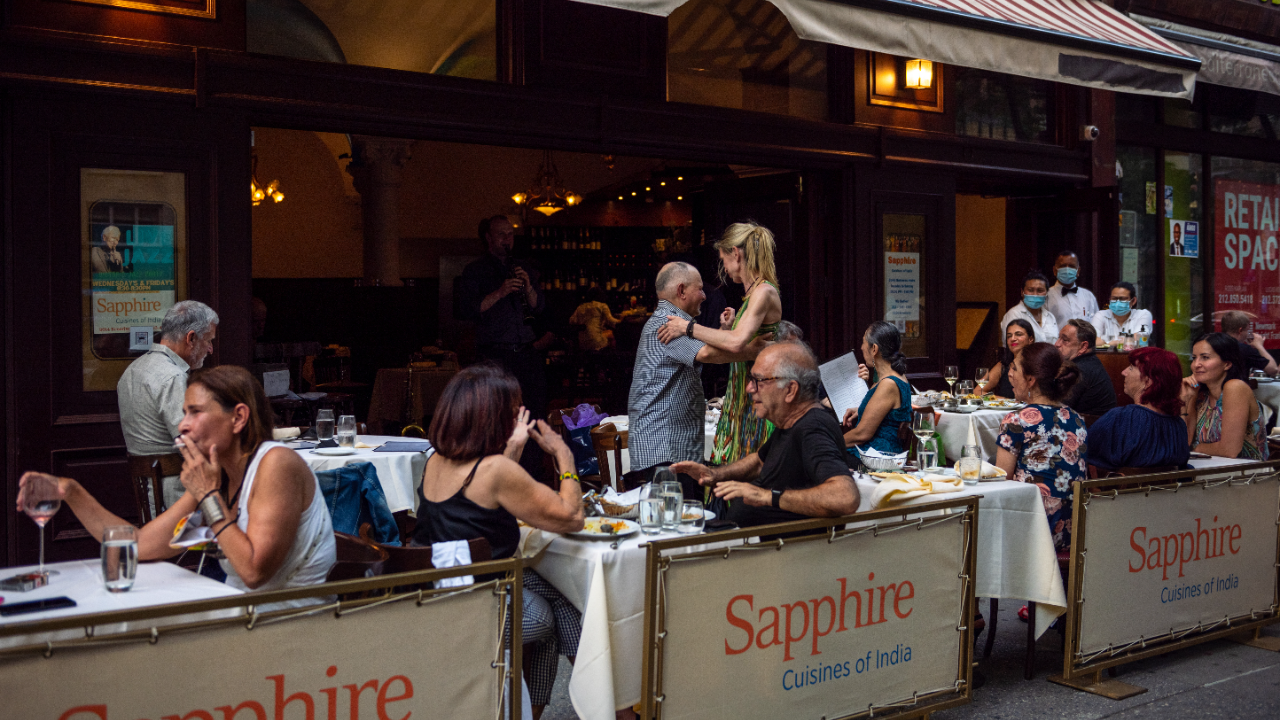 People dance at Sapphire's outdoor dining as musicians play live music on the Upper Wes Side on June 6 in New York City