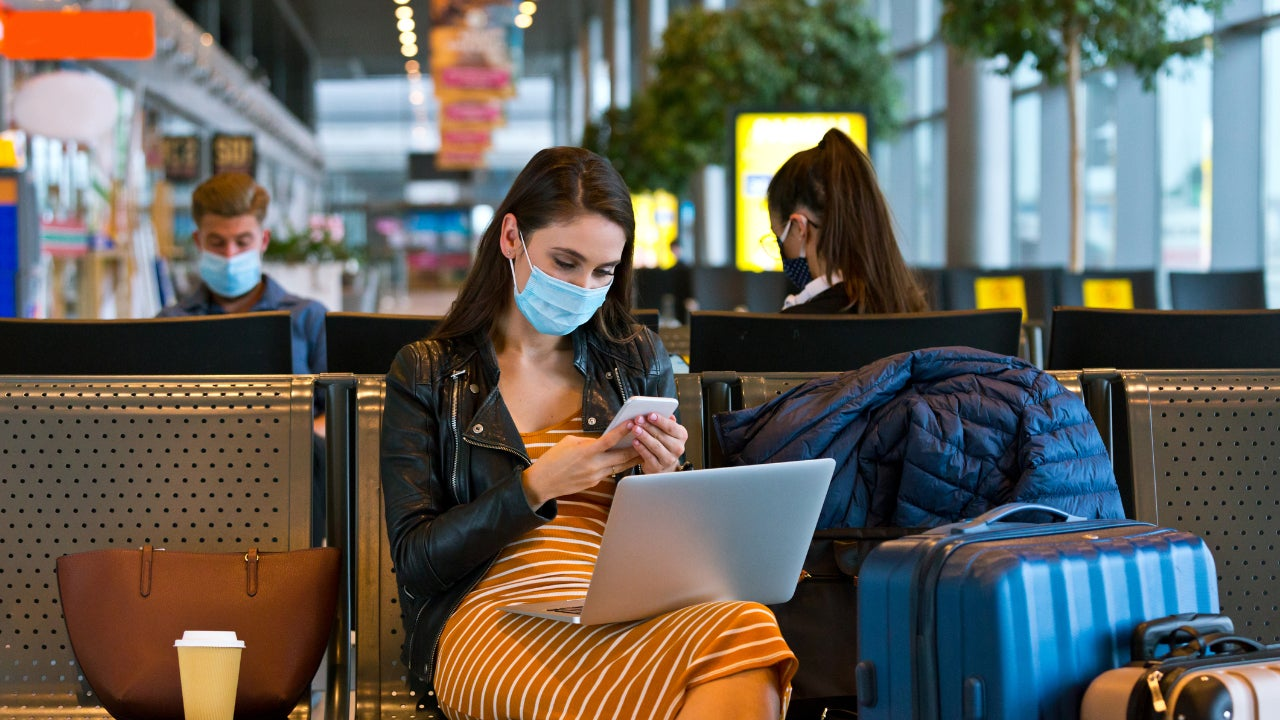 Woman in mask on a smartphone in airport
