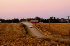 Illuminated Car Moving On Road Amidst Agricultural Field Against Sky During Sunset
