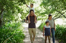 A young couple walk in the woods with their two kids