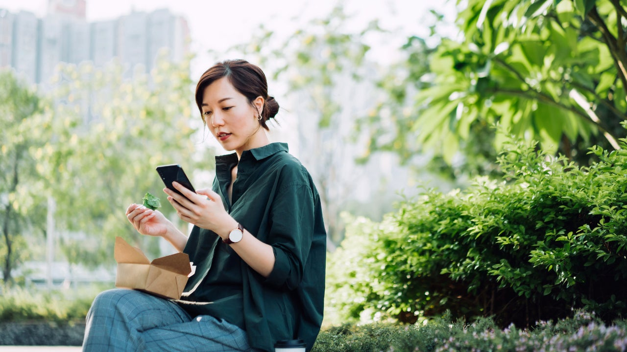 Woman eating lunch and looking at smartphone