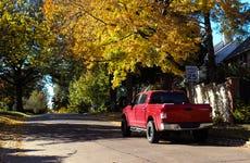 Red pickup truck parked on leafy neighborhood street in Autumn