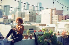 Woman checking smartphone on rooftop