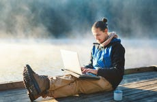 Young man working on his laptop in the nature. Leisure activities / Remote working concept.