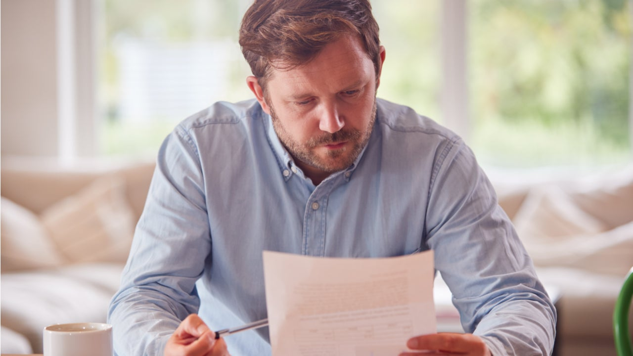 Man looks with concern at paperwork