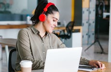 woman works on laptop with headphones on