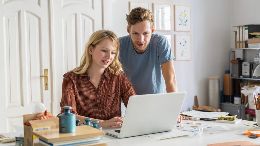 A young couple works on a laptop at home