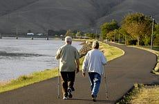Couple walking along water.