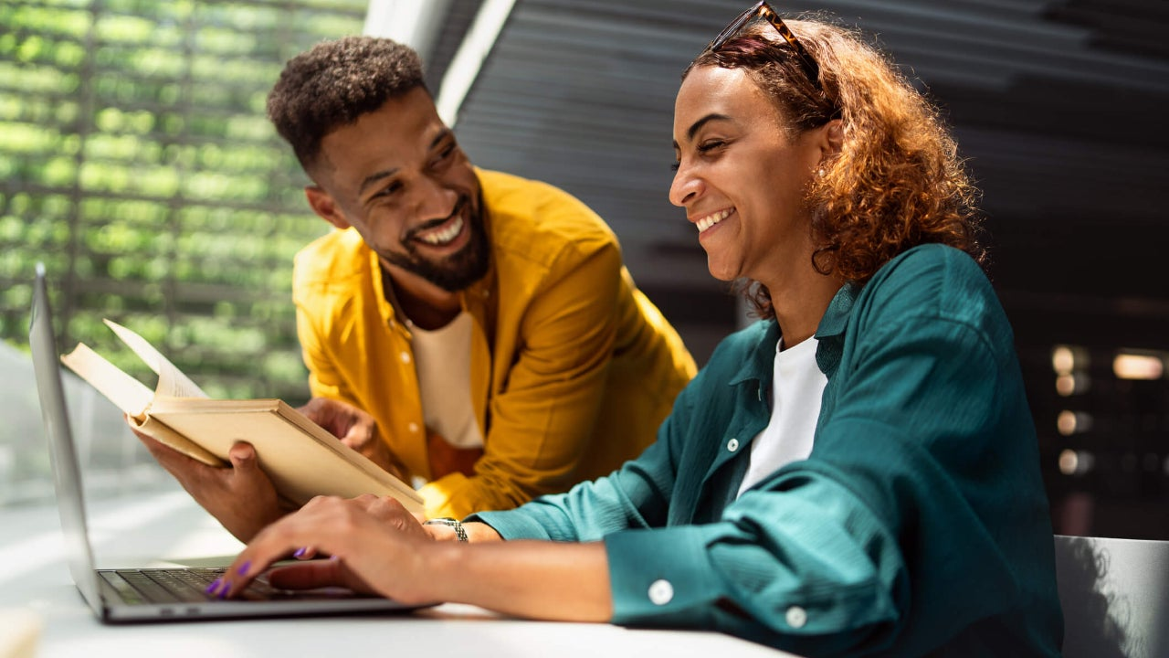 Two university students smile and talk in a library as one holds an open book and the other uses a laptop