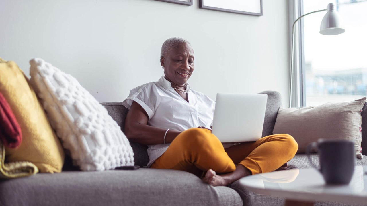 Senior woman using laptop on couch at home