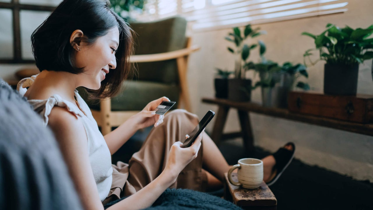 Woman sitting on floor at home shopping online with smartphone while making mobile payment with credit card on hand