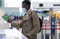 Young man with mask standing at airport ticketing desk
