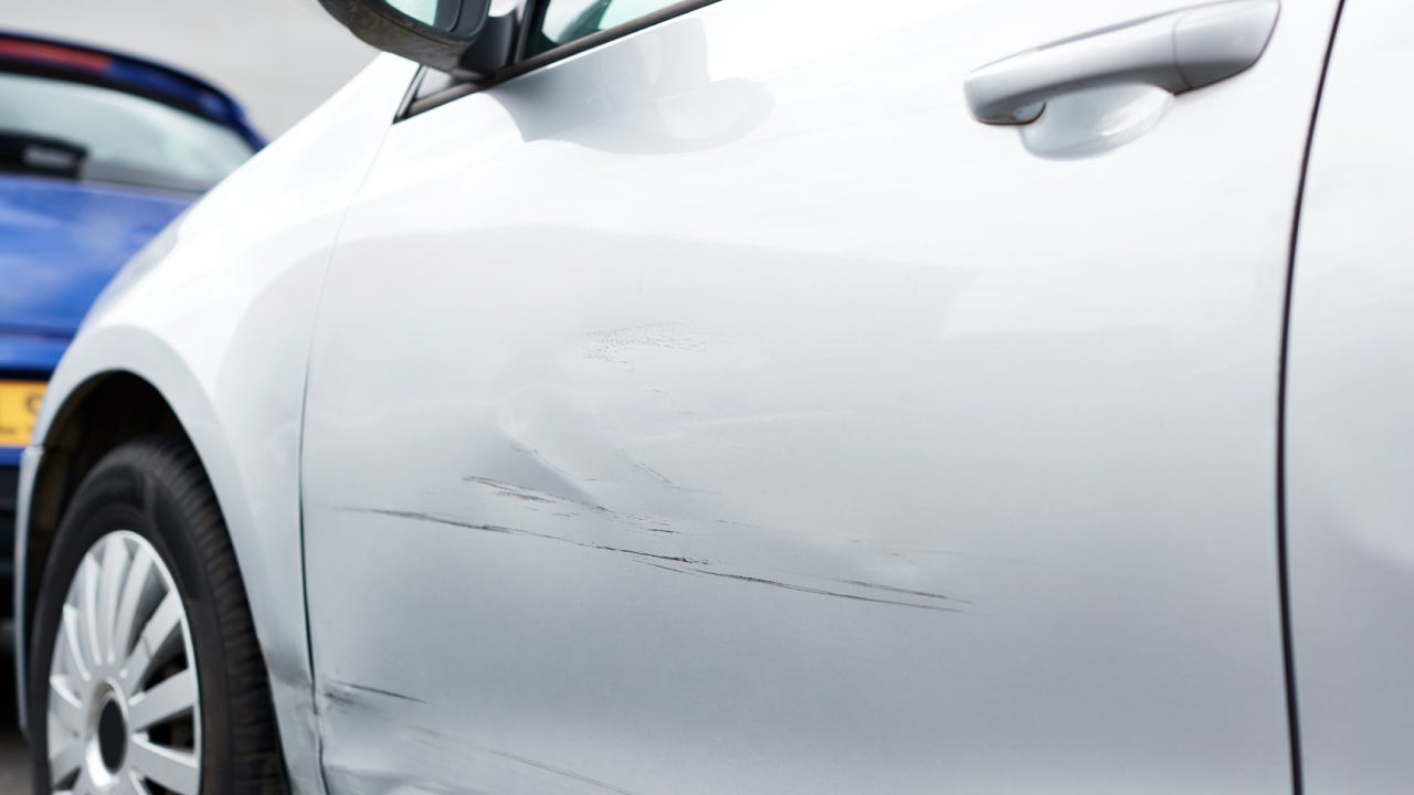 Detail Of Damage To Door Of Vehicle In Car Park With Scratched Panel