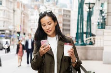 Young woman walks down a city street with coffee while using her smartphone