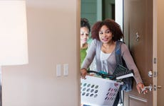 A young woman entering an apartment with her mother, carrying items through the open front door.