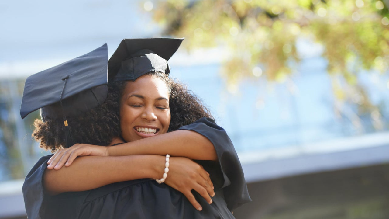 Two college graduates happily embrace