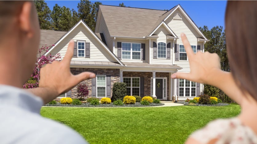 Couple standing in front of home evaluating it