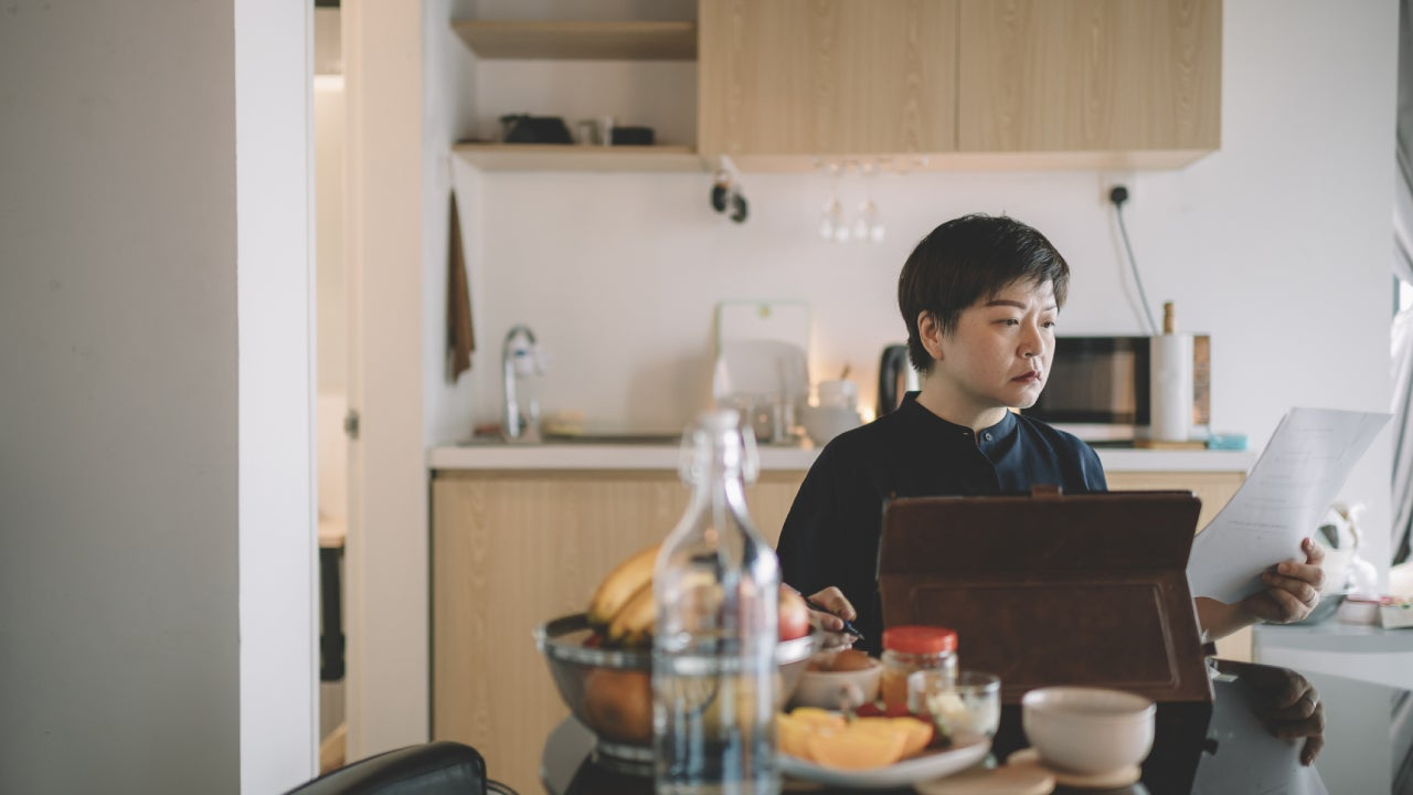 an asian chinese mid adult woman working from home at dining table using digital tablet and documents during breakfast time