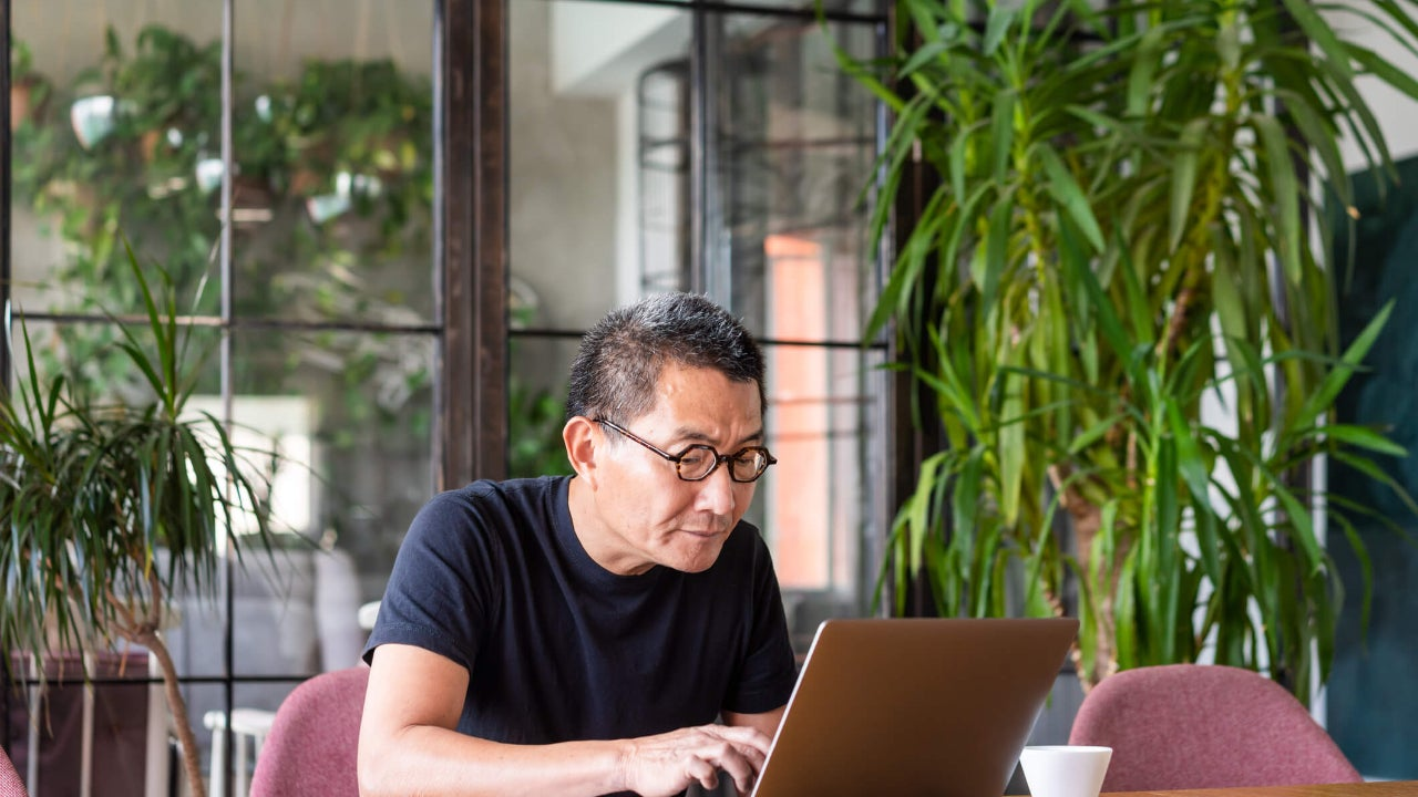 Senior man with glasses uses a laptop at a desk surrounded by house plants