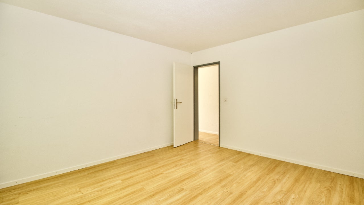 An empty room with light wood floors and white walls