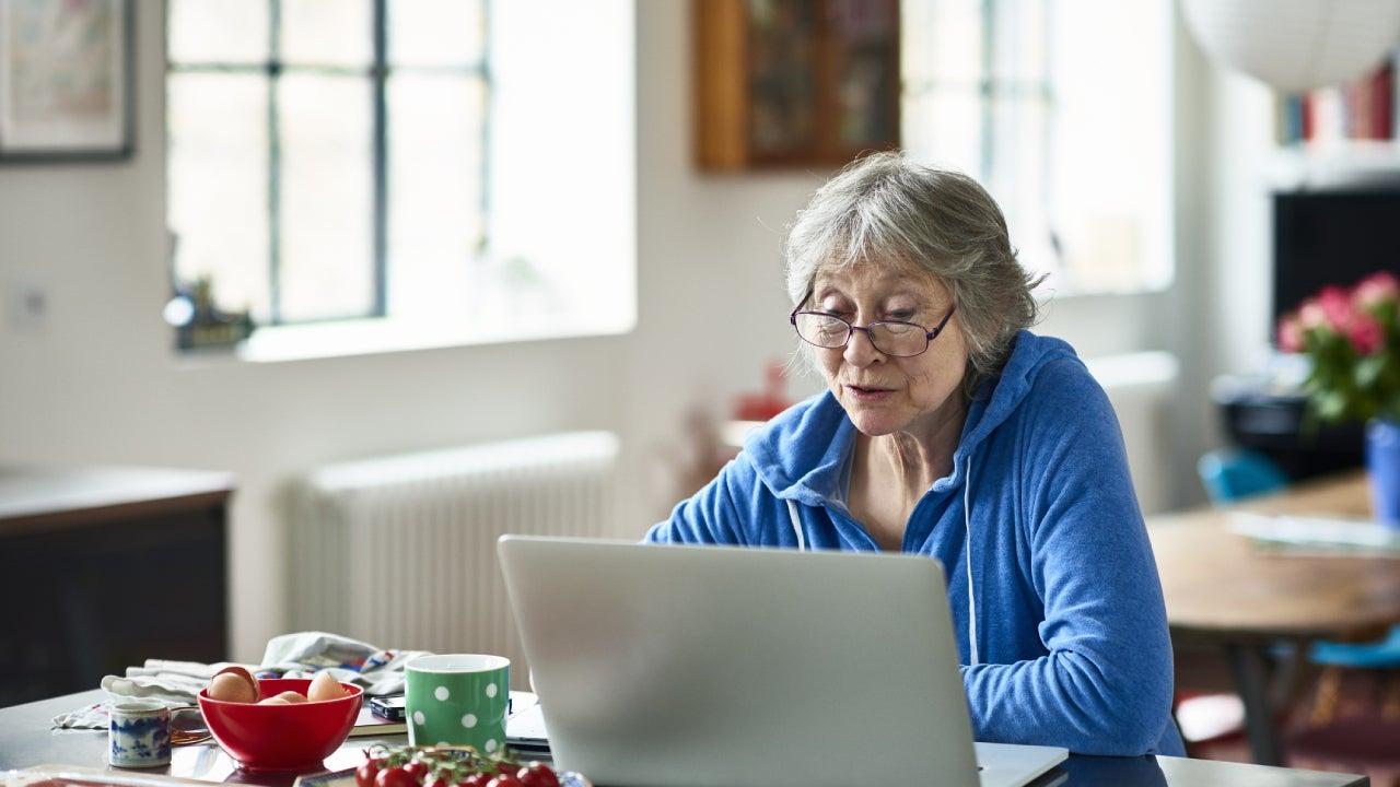 Senior woman wearing glasses using laptop at home