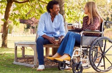 Woman in wheelchair talks with man sitting on a bench