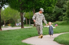Service member walks in the park with young daughter