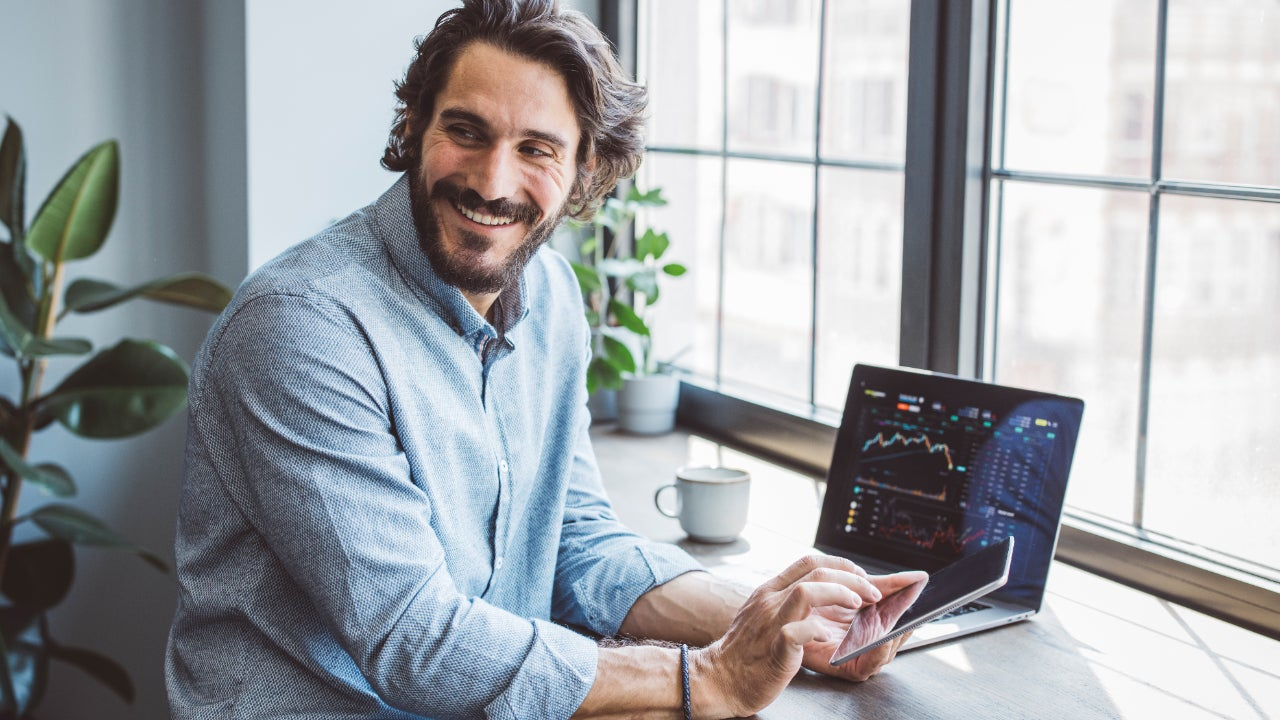 Man at home looking at investments on laptop and phone