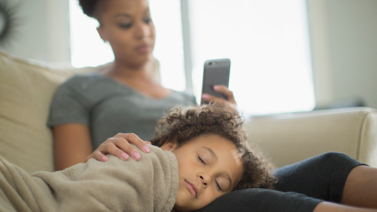 A mother and daughter at home, mother looking at phone, daughter sleeping