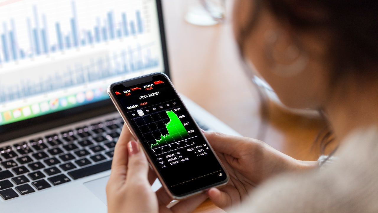 A woman trades stocks on her phone