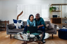 A mature mixed race couple in their suburban home, looking at their laptop