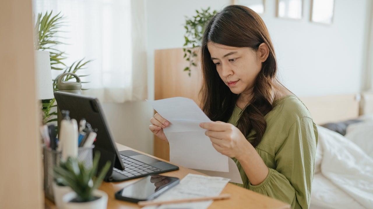 Mother Using Laptop To Check Finances At Home.