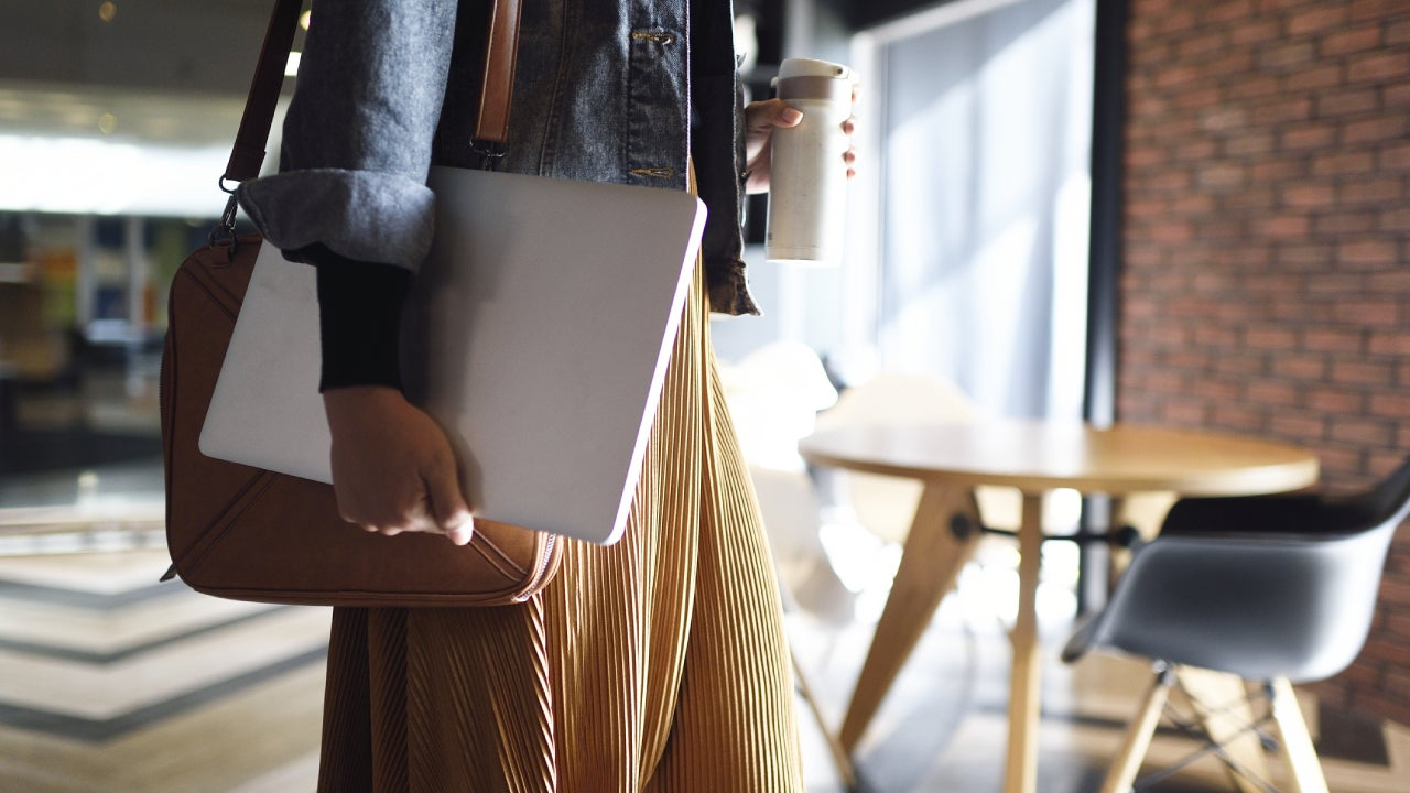 Woman carrying laptop, purse and reusable coffee cup to work