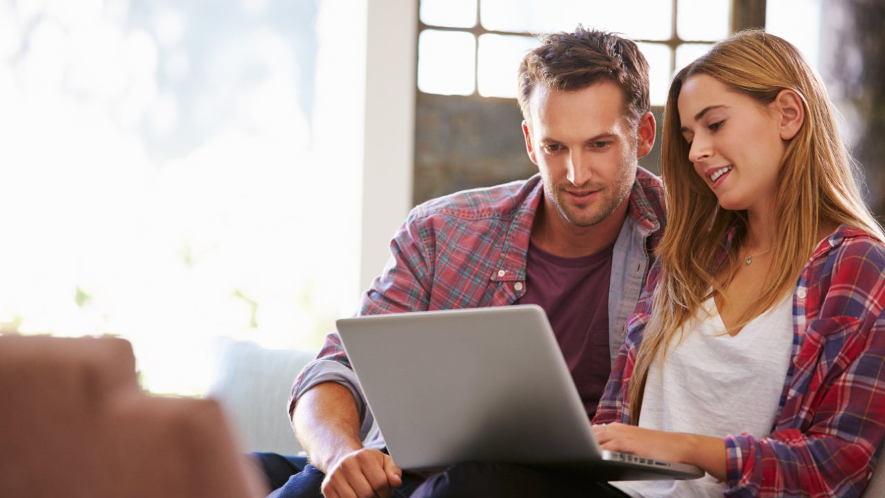 A couple looks at a laptop at home on their couch