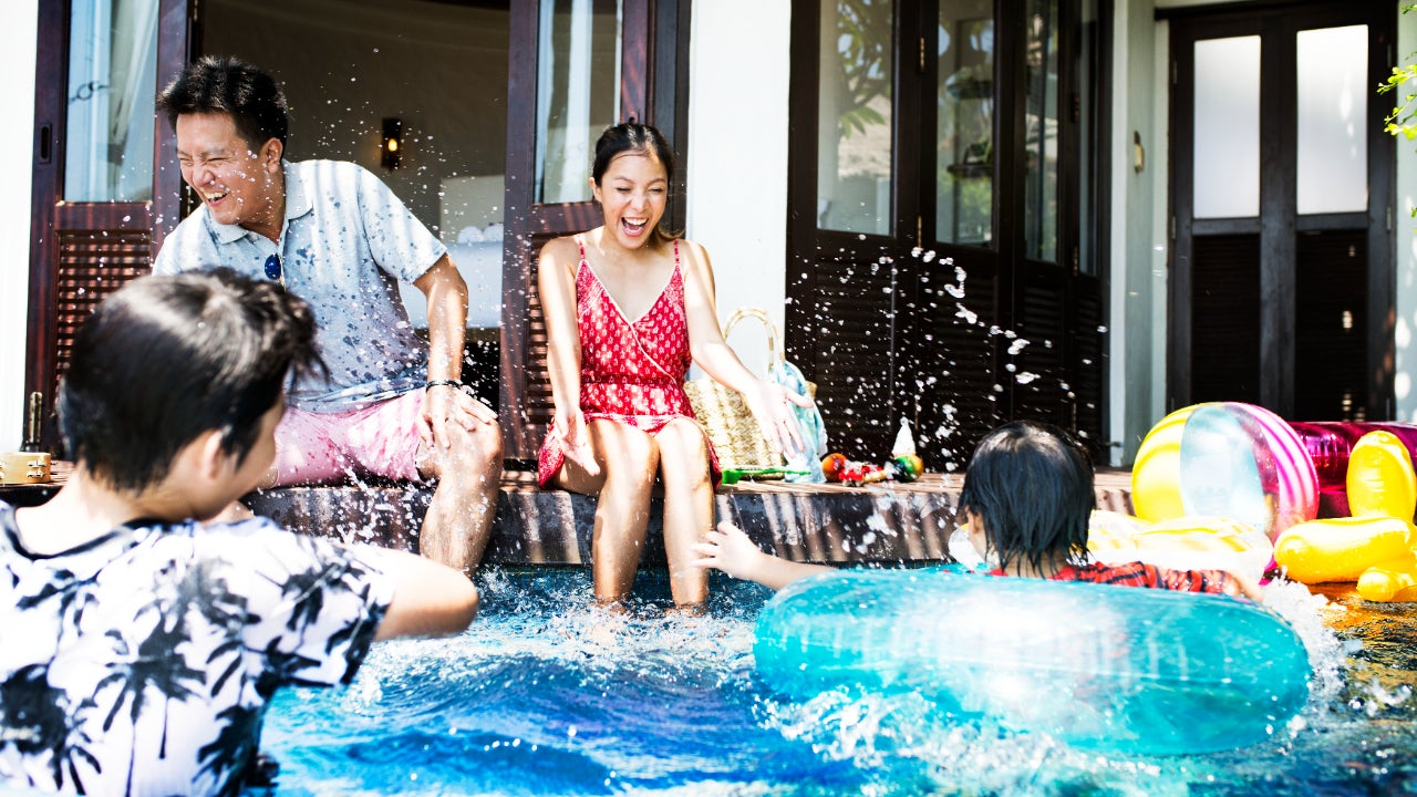 Asian family playing in a pool at home