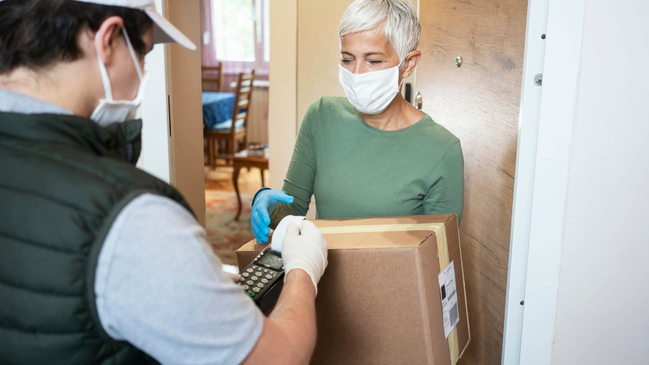 Senior woman accepts package from delivery man at her doorstep